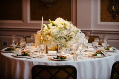 White table scape with white roses floral arrangement. Flowers, Decor & Rentals: River Oaks Plant House | Photography: Adam Nyholt