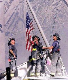 FDNY FIREFIGHTERS RAISING A FLAG OVER THE WORLD TRADE TOWER DISASTER SITE WHERE 343 OF THEIR FELLOW FIREFIGHTERS WERE LOST - SEPTEMBER 11, 2001