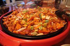닭갈비 (Dalkgalbi). Spicy marinated chicken, rice cakes, vegetables and optional extras such as cheese or noodles, all cooked communally at the table.