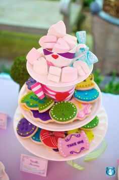 Alice in Wonderland themed cookies perfectly displayed with stacked tea cups and plates.