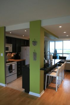 i love the green walls. the white trim. the seating at the kitchen. the huge windows.  The kitchen needs to be just a tad larger and it'd be perfect. <3