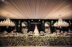 Mesa de doces toda ornamentada com flores brancas e muro inglês ao fundo - Decoração branca por João Callas - Foto Mansano Fotografia