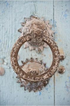 rusty round door knocker on pale blue wooden door
