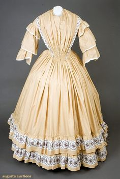 Mustard striped day dress, c. 1848; plum floral on white border print, pointed fan front waist, center front opening with thread eyelets and brass hooks, nine decorative china buttons, bodice lined in white muslin, sold in 2007 for 632 dollars.