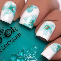 Beautiful blue hues of color on white nail polish to create the design of butterflies, bees, and floral petal leaves. #beautynails