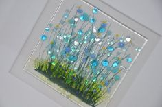 This Cornflower picture is made in my kiln in my home studio in North Wales. The piece is then fired for 12 hours at approx 800c to fuse the glass and paints together. The frame surrounding my picture is an off white which sets off the blue perfectly. Glass tile is approx 10cm x 10cm, surrounded by a double mount. The frame is approx 25cm x 25cm. Each piece is individually painted and made so variation from the picture should be expected.