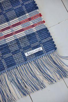 """trasrips, även kallad glesrips, med sin flerdimensionella uppbyggnad. Här långrandig med små """"flaggor"""" av varpen (oblekt och blå) och bredrandig av inslagstrasorna, varannat parti ljusblå trasor och varannat parti mörkblå trasor."""