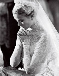 Grace Kelly, in a gown by MGM costume designer Helen Rose, kneeling at the altar. Photo: Bettmann/Corbis