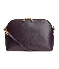 Pflaume. Handtasche aus geprägtem Lederimitat. Die Tasche hat einen schmalen abnehmbaren Schulterriemen und oben einen Reißverschluss. Ein Innenfach mit Rei