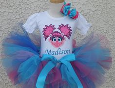 For your next perfectly fabulous Abby Cadabby Birthday Bash! Here is the perfect tutu for your little girl who loves Abby Cadabby. You get an embroidered onesie or tee with Abby Cadabby on it and your child\'s name.   The tutu is full and fluffy. This super cute birthday tutu set will be perfect for your little girls birthday party! The full set includes a personalized onesie or shirt with a 8.5\ tutu and ahair bow on a headband (included)or 2 bows on clips ( 1st Birthday Tutu, Little Girl Birthday, Birthday Dresses, Birthday Bash, Birthday Party Invitations, Birthday Party Themes, Birthday Ideas, Pumpkin Outfit, Abby Cadabby