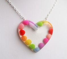 A clear glossy heart shaped resin pendant, carefully filled with an array of beautifully coloured candy-like adornments that I have placed by hand