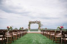 Fruitwood folding chairs used in a wedding ceremony with a floral arch
