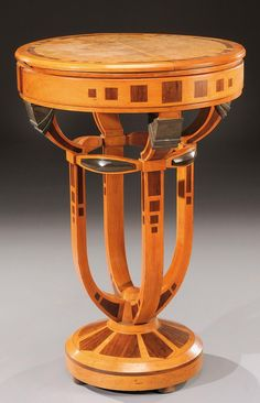 Pedestal table in mahogany and exotic wood veneer with a circular top, opening by two hatches. Circa 1930.
