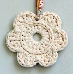 A crochet flower deco – A perfect way to use T-shirt yarn leftovers You can hang one romantic flower on your wall, create a flower bunting or join them to a runner or a rug etc. Materials: T-shirt yarn A suitable crochet hook A tapestry needle Decorative strings / cords. Instructions: Create a magic ring …