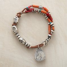 "LIMITED EDITION CORAL BRACELET -- Sandy brown leather links chunky sterling silver beads with rare, ancient Tibetan coral, antique Venetian glass ""whitehearts"". Wild horse charm inscribed ""beauty"" dangles near lobster clasp. Signed by Jes MaHarry. Limited edition. 7-1/2""L."