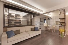 All furniture in the home fits within the neutral, natural hued framework of the design, including the lengthy sofa here below a set of wraparound windows defining a home office. Kitchen can be seen in background.
