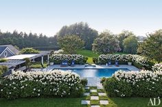 {This gorgeous pool surrounded by hydrangea hedges is the very picture of Hamptons idyll thanks to designer, Juan Montoya. | Image via Architectural Digest}
