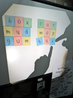 From First Grade Fresh. I've done this with a good ol' low-tech overhead projector set on the floor by a wall, and the kids loved it! Of course, you could do the same thing with a doc camera, and wouldn't even need the transparent tiles.