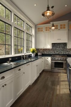 Gorgeous transitional kitchen. Nautical style pendant, white cabinetry and vaulted ceiling