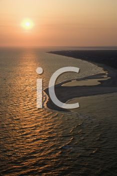 iCLIPART - Royalty Free Photo of an Aerial View of the Sun Over the Atlantic Ocean and Shoreline of Bald Head Island, North Carolina