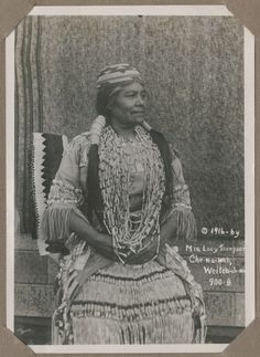 """Mrs. Lucy Thompson, Che-na-wah Weitch-ah-wah (1916) Handwritten on verso – """"This picture was taken in May 1916 in a new Indian dress that I made myself and I wore it at the Sweet-Pea Carnival in the Lumbermans Association's float and took first prize."""" Lucy was a member of the Yurok Tribe. She was born in 1856 in the Pecwan Village, which is on the Klamath River near the mouth of Pecwan Creek. 1916, Lucy wrote the book To the American Indian, in which she describes ..."""