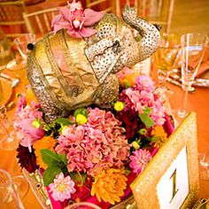 Baskets of blended flowers are paired with elephant figurines at this exotic reception.