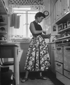 Career girl and hostess Joan Wilson cooking in the kitchen. Photograph by Nina Leen, 1950.