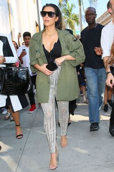 Kim Kardashian shopping on Rodeo Drive in Beverly Hills wearing custom silver-beaded Balmain pants, a black tank, and a green cargo jacket.