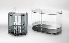 6000 Fumé and 9000 Fumé bar trolleys with curved sides in transparent or smoked glass 1cm thick, shelf options in Italian walnut, cherrywood or wenge with transparent or sandblasted middle shelf, two sizes 55cm diam x 60cm and 90cm x 56cm x 60, by Reflex, from £1820-£2200, Chaplins