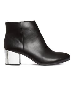 Ankle boots in imitation leather with shiny metallic heels, concealed side zip, and rubber soles. Satin lining. Heel height 2 1/4 in.