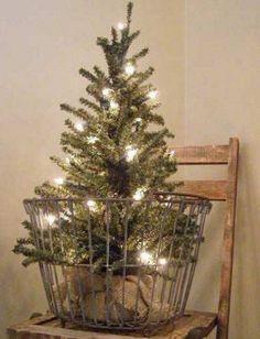 Необычная елка в винтажной корзине для яиц, украшена только светящейся гирляндой. .