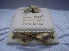 Square golden 50th wedding anniversary cake with delicate sugar roses spray finished with a large golden ribbon and bow