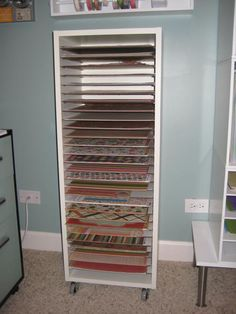 Scrapbook paper storage - org. poster said she built it from Akurum kitchen cabinet with shelf pegs in every hole. Paneling cut into 28 pieces @ 11 1/2 x 13 3/8.