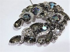 ITEM # 121660  Antique 1950s unsigned WEISS (verified) smoky grey Black Diamond as was called by Weiss, peacock aurora borealis crystals and pave rhinestone brooch. This brooch consists of 6 medium faceted glass rounds with the peacock aurora borealis finish, 5 large black diamond faceted glass navetttes, 1 medium black diamond faceted glass navette, 15 varied sized black diamond faceted glass rounds, 4 medium crystal faceted glass rounds and a black diamond faceted glass fancy cut, and 46…