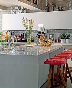 A bancada de mármore cinza acompanha o design moderno da cozinha, criação do arquiteto Nelson Kabarite. Os bancos de assento vermelho quebram a neutralidade