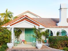 Aside from a fresh island green on the trim and front door, the home's exterior remains just as it was—a low-slung Lyford Cay bungalow with a terra-cotta shingle roof, tiered gabled portico, and circular tile driveway.