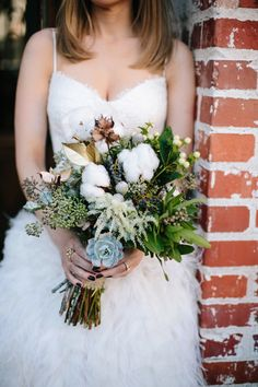 The bride's bouquet featured florals, succulents, cotton, and foliage that looked freshly picked from the garden with accents of gold-dipped leaves. Photography: Heather Kincaid. Read More: http://www.insideweddings.com/weddings/monique-lhuillier-operations-manager-hannah-lyons-unique-wedding/565/