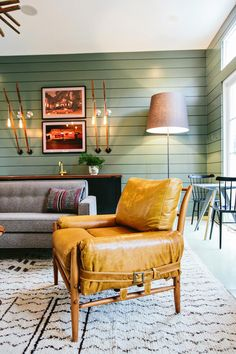 This green living room includes a leather chair that has a weathered look, giving the space a rustic vibe. The green paneled walls, paired with midcentury modern furnishings, give this space a rustic yet modern feel.