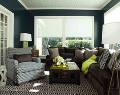 A sophisticated family room just off the kitchen with big windows and lots of natural light. The combination of beautiful chocolate brown, navy blue high gloss walls, and lime green really pops. Photo by @David Livingston and design by Annie Lowengart.