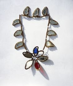 """Calder Necklace, c. 1938. Brass wire, glass, and mirror Loop: 35 1/2 inches; flower: 8 x 8 inches   Inscription: """"CS""""  Private Collection, New York"""
