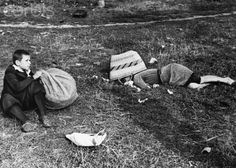 """A boy sits beside the body of his mother, killed in a German air raid as she worked in potato fields in Poland, 1939."""
