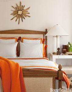 Orange bedding accents brighten a white guest room in a San Francisco row house decorated by Benjamin Dhong.