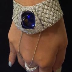 A spectacular tanzanite set among a sea of diamonds to create a silky bracelet with attached ring for a classic look with modern twist! @karen.suen