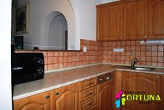 Kuchyňský kout v rodinném domě, opticky oddělený od obývacího pokoje vyzděným obloukem