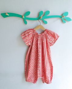 An old school romper suit, perfect for all occasions.  This one is  made from the most incredible red cotton lawn that is lightweight and super soft to the touch.  These  rompers are  easy to put on, with poppers allowing it to be over the  head (made even  easier with an elastic neckline). It's easy to wear all  year long, with  tights and a cardy in the colder months and on it's  own in the  summertime. The baggy fit means that it's super comfortable and perfect for crawling or rolling ...