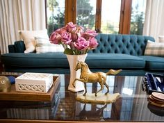 Tufted blue sofa and coffee table vignette in the Hollywood Regency style.