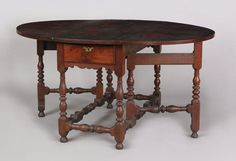 """Large Southeastern Pennsylvania William & Mary walnut gateleg dining table, ca. 1730, the oblong top supporting two demilune leaves, above a frame with 2 drawers and scalloped skirt supported by baluster and ring turned and blocked legs joined by stretchers, retaining an old mellow finish, 29 3/4"""" h., 45 1/2"""" w., 59"""" (open). Exhibited at the Philadelphia Art Museum October 7, 1982 - January 7, 1983. A copy of correspondence regarding this exhibit accompanies the lot. Provenance: John Walton."""