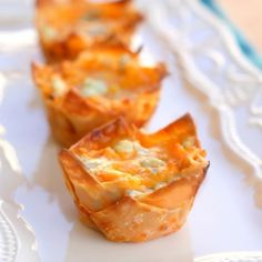 Buffalo Chicken Cupcakes  1 (8 ounce) package cream cheese, softened   1/2 cup Ranch dressing   1/2 cup Buffalo wing sauce (Frank's is the brand I like)   1 cup shredded cheddar cheese, divided   1 1/2 cups cooked and shredded chicken   24 wonton wrappers (see Note)   1/4 cup blue cheese crumbles