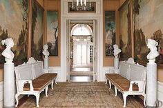 Circa-1800 French riverscapes share the garden hall with antique marble busts depicting the four seasons; the painted benches were designed in the manner of 18th-century British architect William Kent.