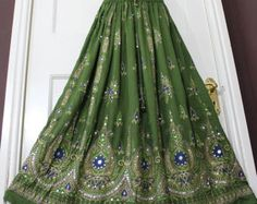 Rayon Fabric printed ethnic vintage look Skirt long skirt with lots of hand sequin work · Length - 2 Panel Waist with elastic and string Free One Size For XS / S / M /L (U.K. Size 8, 10, 12, 14) · 100% Rayon · HAND WASH IN COLD WATER OR DRY CLEAN Elastic Belt=26 Inch Relax and 46 Inch after Stretched Also have string to tie waist with cute tiny bells at the end of the string. Length : 37 inches without lining · This is manual tie dye skirt and took image of one ski...